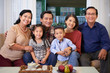 canvas print picture - Portrait of happy big Vietnamese family sitting on sofa and smiling at camera