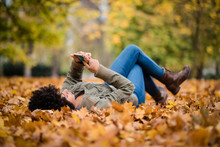 Teen Girl Using Her Mobile While Lying In The Park