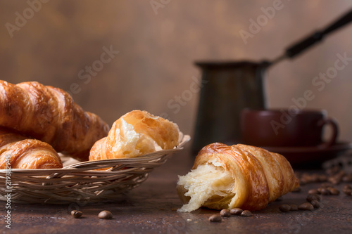 Photo Fresh and tasty croissant  and cup of coffee on old copper background