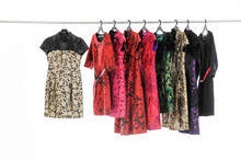 A Row Of Evening Gown Clothes Hanging On Hangers