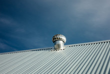 New Stainless Steel Air Ventilator On The Metal Roof Against Blue Sky.
