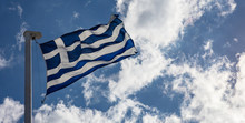 Greek Flag On Flagpole Waving On Blue Sky Background
