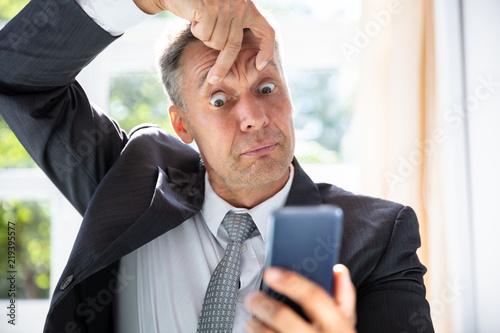 Cuadros en Lienzo Terrified Businessman Looking At Mobile Phone Screen