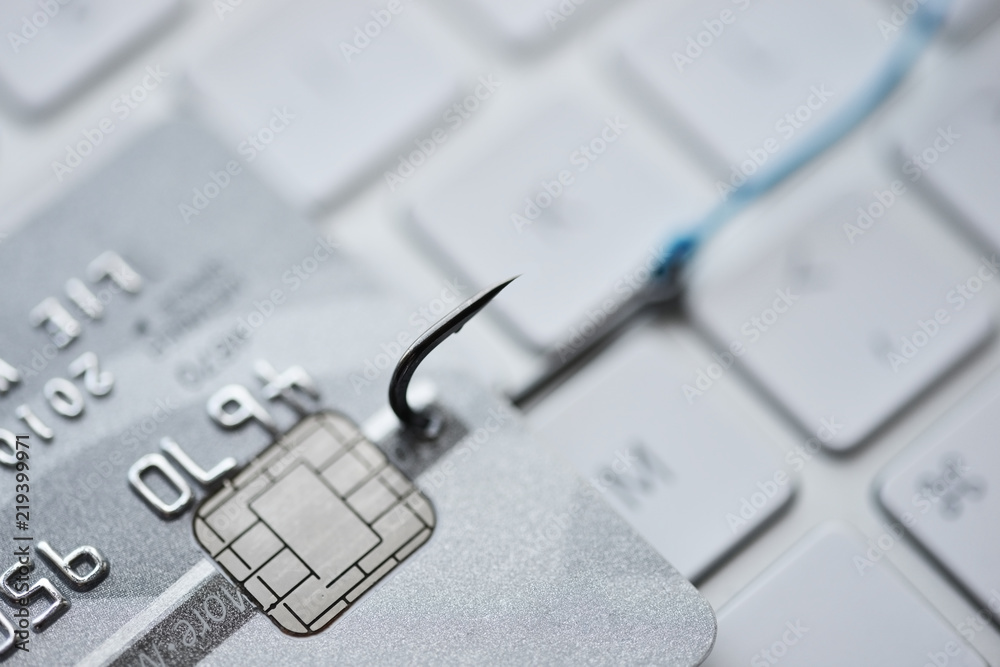 Fototapeta Hacking and phishing attack on internet concept with credit card on fishing hook on computer keyboard