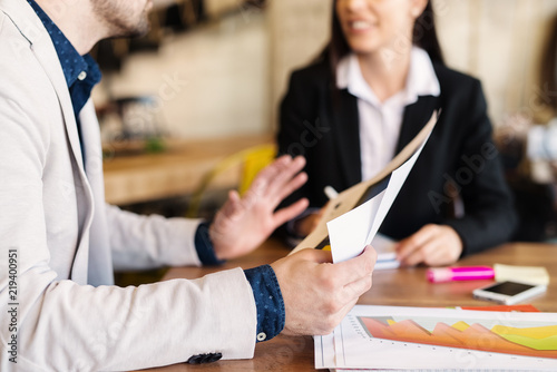 Fototapety, obrazy: Close up of man hands holding documents while he is sitting in a business meeting .Table full of histogram and gadgets.