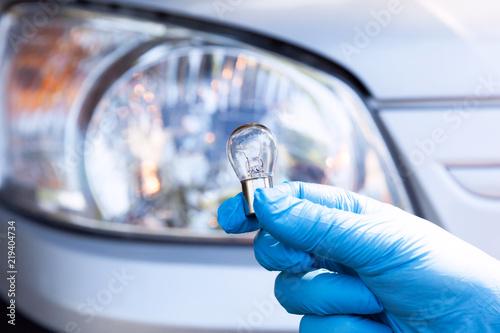 Close up of a light bulb with car headlight in the background