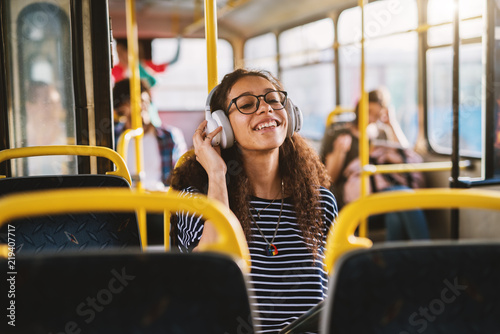 Fotografie, Obraz  Curly smiling girl enjoying music in bus.