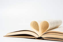 Close Up Of Opened Book With Heart Shaped From Two Pages, Isolated On White Background.
