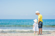 Boy and girl standing holding hands on the beach on summer holidays. concept of summer family vacation. Space for text