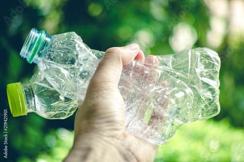 Valokuva  close up of hand holding used crashed plastic bottle for recycling