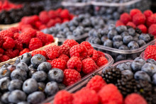 Fresh Forest Raspberries, Blueberries And Blackberries In Plastic Trays At Market. Background.