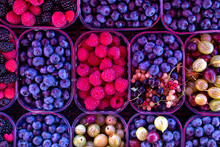Background Of Forest Fruit And Berries In Plastic Trays At Market.