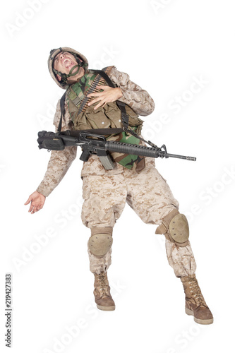 Fotografía  Studio shoot of army soldier in combat uniform and body armor, screaming, clutching chest, dropping weapons and falling down after being fatally shot in military firefight