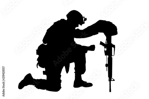 Canvas Print Army soldier in sorrow for fallen comrade, standing on knee, leaning on rifle with helmet and two dog tags on chain, studio shoot isolated on white low key silhouette