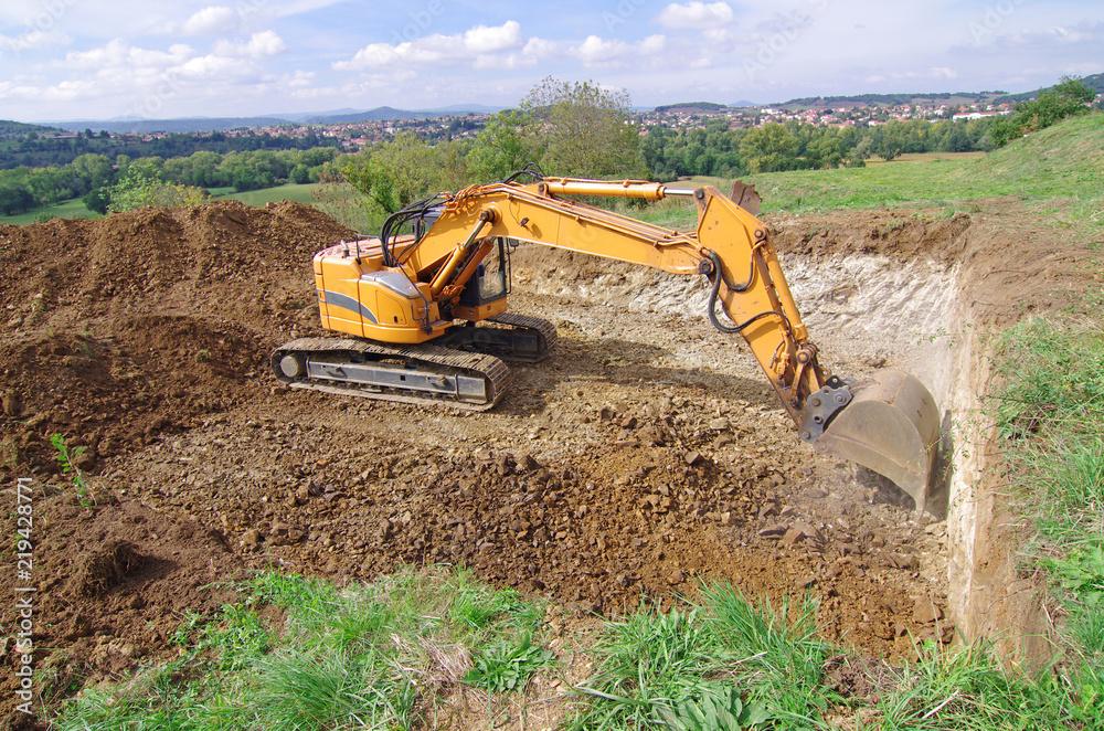 Fototapeta Pelleteuse à godet et à chenille en action, terrassement en vue de la construction d'une maison. Pelle mécanique hydraulique