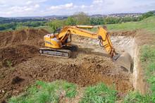 Pelleteuse à Godet Et à Chenille En Action, Terrassement En Vue De La Construction D'une Maison. Pelle Mécanique Hydraulique