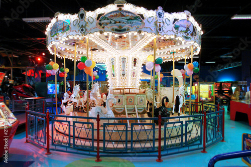 Colorful big carousel with horses and swans