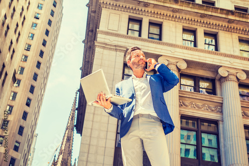 Fotografie, Obraz  Young European Businessman with beard traveling, working in New York City, wearing blue blazer, gray pants, standing outside old office building, working on laptop computer, talking on cell phone
