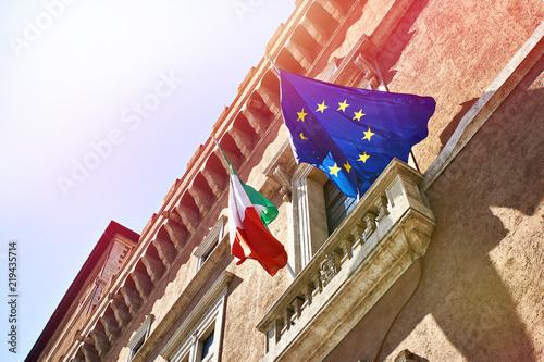 Fototapeta premium Flagi Włoch i Unii Europejskiej na tle niebieskiego nieba