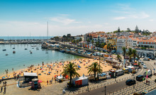 High Vantage Point Of Crowded Sandy Praia Do Ribeiro And Boats On Bay A A Sunny Summer Day. Cascais Is A Small Quaint Village 30km West Of Lisbon