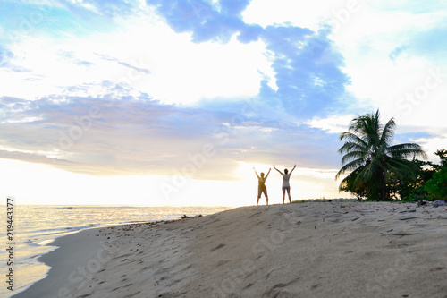 Foto  two women walking on the beach at dawn