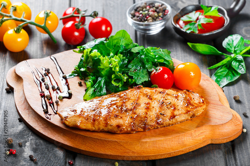 In de dag Buffet, Bar Grilled chicken fillet with fresh vegetable salad, tomatoes and sauce on wooden cutting board. Hot Meat Dishes. Top view