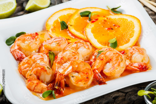 Honey Glazed Shrimp with orange slices, spices and sunflower sprouts on white plate on bamboo background Canvas Print