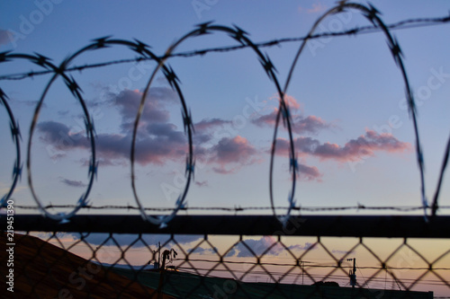 Fotografiet  sunset with clouds and silhouettes of fences