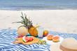 Beach picnic with lemonade and fruits (pineapple, grapefruit, kiwi, watermlon, cantaloupe, mango)