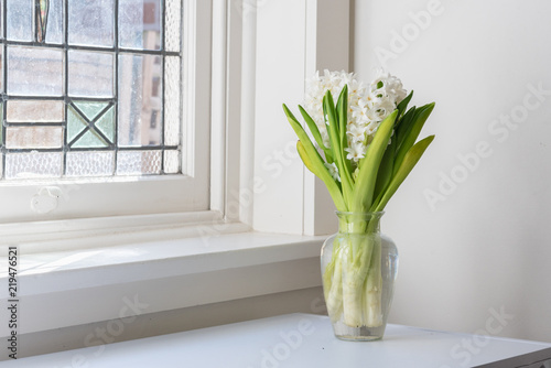 White Hyacinths In Glass Vase On Table Next To Vintage Window