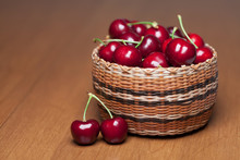Red Ripe Cherries In A Basket On A Wood Table