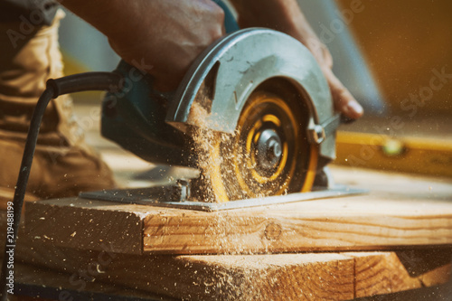 Obraz Close-up of a carpenter using a circular saw to cut a large board of wood - fototapety do salonu