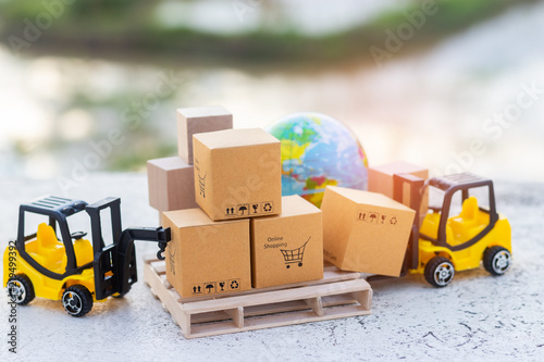 Fototapeta Mini forklift truck load cardboard box with shopping cart symbol on wooden pallet and globe near by. Logistics and transportation management ideas and Industry business commercial concept. obraz