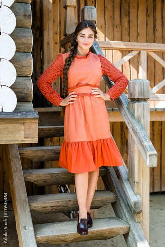 Fényképezés  A girl in a red dress made of flax, a long braid, a Russian beauty, a rustic sty