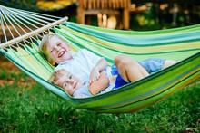 Two Happy Blond Scandinavian Children Swinging And Relaxing In Garden Hammock Together.
