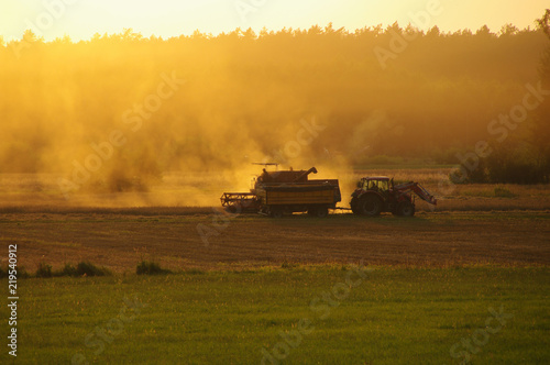 Staande foto Meloen Harvester against hot orange sunset background