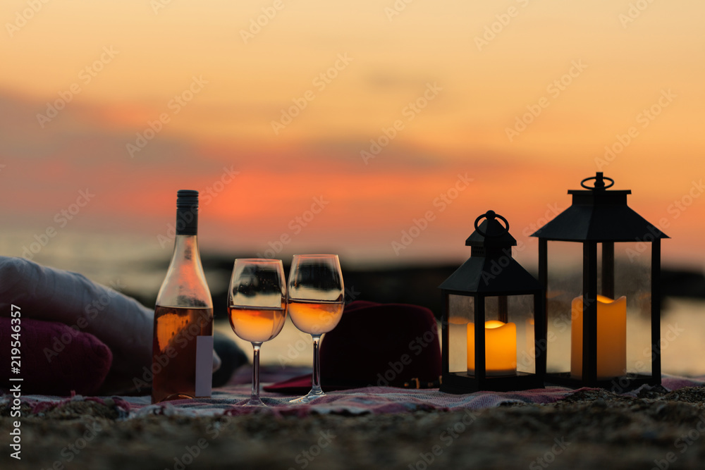 Fototapety, obrazy: Summer sea sunset. Romantic picnic on the beach. Bottle of wine, glasses, candles, plaid and pillows.