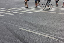 Pedestrians Crossing City Street With White Zebra Lines And Empty Asphalt Road Background. Pedestrian Crosswalk View With People Legs And Bike On City Street, Zebra Crossing Point With Walking People