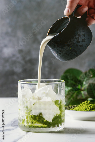 Fotografía Cream pouring from jug to matcha green tea iced latte or cocktail in glass, with ice cubes, matcha powder on white marble table, decorated by green branches