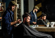 Barber styling hair of brutal bearded client with clipper. Barber with hair clipper works on hairstyle for bearded man barbershop background. Hipster client getting haircut. Hipster lifestyle concept
