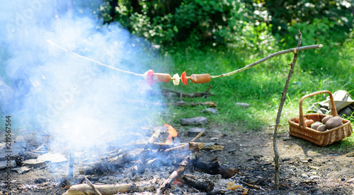 Keuken foto achterwand Picknick Roasting food on stick. How to roast sausages with vegetables. Sausages on stick bonfire background. Roasty toasty sausages are such quintessential taste of picnic. Smoky smell of roasted food