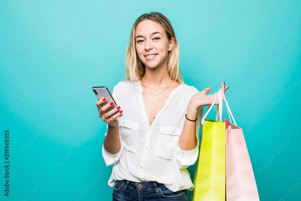 Fototapeta Portrait of a happy young woman holding shopping bags and mobile phone isolated on a mint background