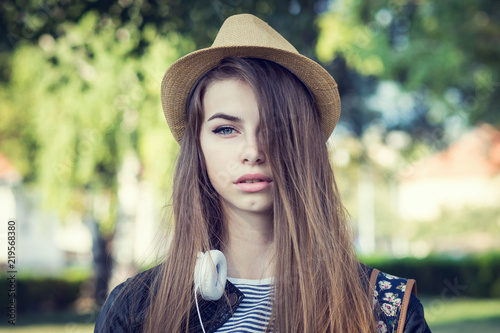 Fotografie, Obraz  Young woman with blue eyes and long hair, headphones and hat, outdoors in park