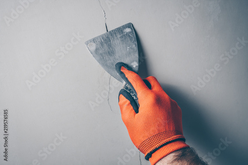 Fototapeta Worker repairs a crack in the wall from shrinkage of the building or poor-quality work obraz