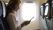Business woman in airliner texting in smartphone