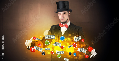 Foto  Young illusionist in tails hold between hands gambling staffs with super power