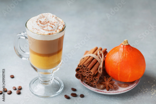 Pumpkin spiced latte or coffee in glass. Autumn, fall or winter hot drink.