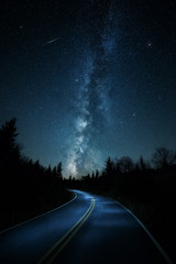 Curvy road with shooting star and Milkyway above