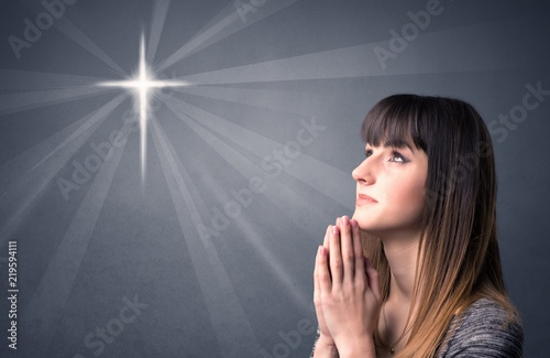 Fotografia  Young woman praying on a grey background with a shiny cross silhouette above her