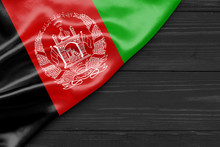 Flag Of Afghanistan And Place For Text On A Dark Wooden Background